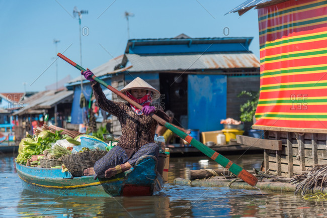 Kompong Luong Floating Village, Krakor District, Cambodia - 12 August 2014: Khmer Women Rows Through Cambodian Floating Village With Fresh Vegetables To Sell..