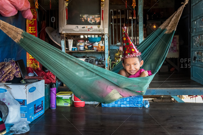 Kompong Luong Floating Village, Krakor District, Cambodia - 12 August 2014: Young Khmer Boy Lying In Hammock With Party Hat On In Cambodian Floating Village.