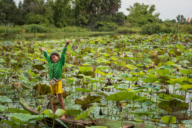 Lotus Pond, Battambang Province, Cambodia - 14 August 2014: Young Child Plays In Old Wooden Fishing Boat In Lotus Pond.