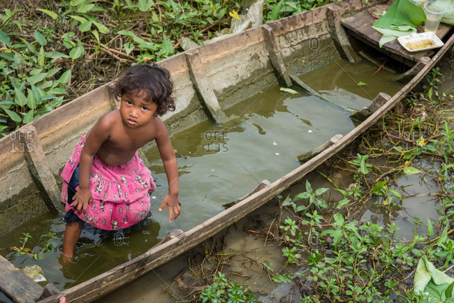 Pond, Battambang Province, Cambodia - 14 August 2014: Young Child Plays In Old Wooden Fishing Boat In Dried Up Pond.