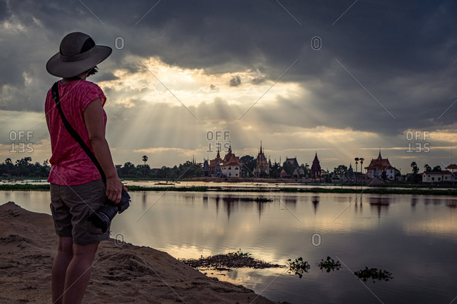 Sunrays, Temple Complex, Kandal Province, Cambodia - 19 September 2014: Photographer Admires Sunset Rays Over A Temple Complex With Reflection In Water Pool.