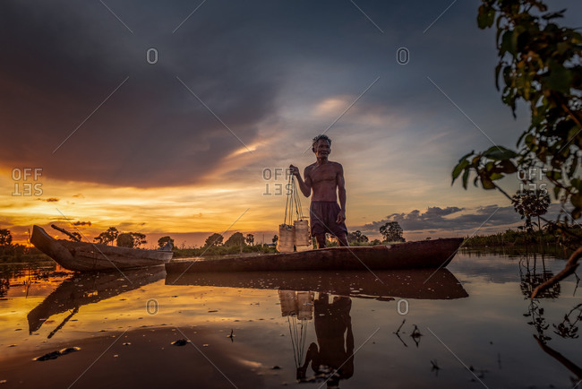 Silk Island (Koh Dach), Cambodia - 21 October 2014: Old Khmer Man Prepares Plastic Containers In Dug-Out Wooden Canoe To Collect Sugar Palm Juice.