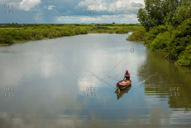 Small Wooden Boat On The Water, Battambang Province, Cambodia - 25 October 2014: Fisherman Looking For The Right  Place To Throw Net.