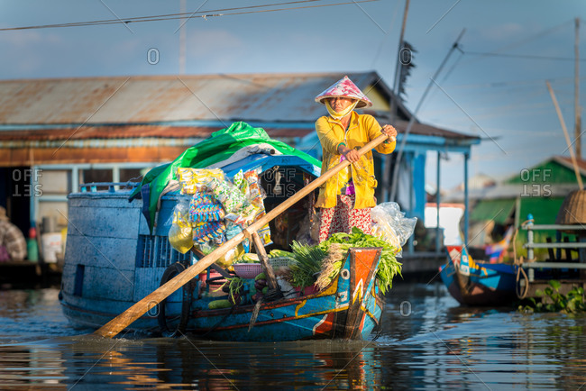 Floating Village, Kompong Chnang, Cambodia - 15 December 2014: Lady Rows Her Floating Shop Past Houses In Warm Evening Light.