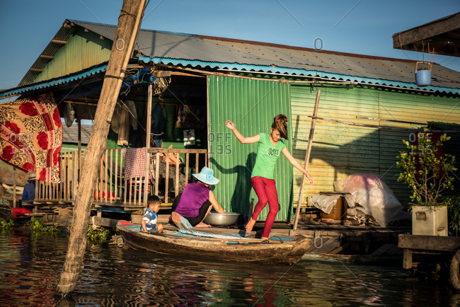Floating Village, Kompong Chnang, Cambodia - 15 December 2014: Family Travel In-between Floating Hoses Using Boats As Walkways.