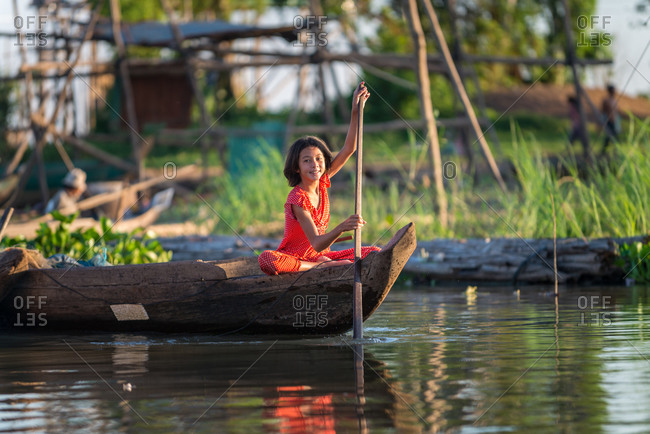 Floating Village, Kompong Chnang, Cambodia - 15 December 2014: Young Khmer Girl Rows Through Floating Village In Warm Evening Light.