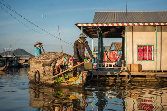 Floating Village, Kompong Chnang, Cambodia - 15 December 2014: Floating Shop Rows Past Houses.