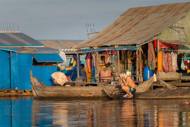 Floating Village, Kompong Chnang, Cambodia - 15 December 2014: Fisherman Washes His Face From Small Wooden Fishing Boat.