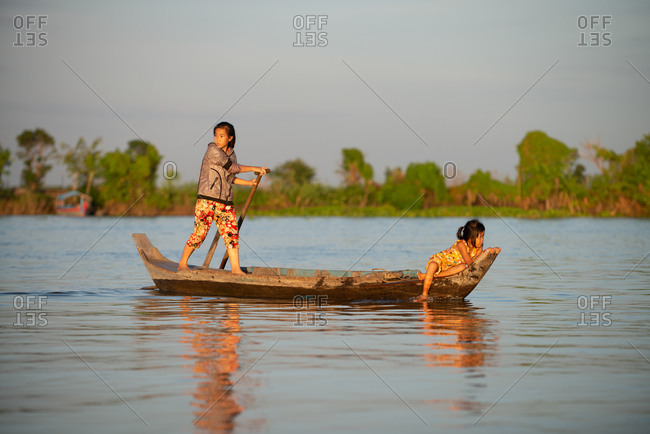 Floating Village, Kompong Chnang, Cambodia - 15 December 2014: Sisters Row Traditional Wooden Fishing Boat Across Open Water To Floating Village.