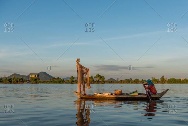 Floating Village, Kompong Chnang, Cambodia - 15 December 2014:  Fisherman Gets Ready To Throw Fishing Net From Traditional Wooden Fishing Boat With Wife Controling The Boat.