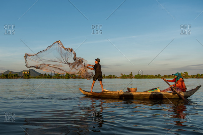 Floating Village, Kompong Chnang, Cambodia - 15 December 2014: Fisherman Throws Fishing Net From Traditional Wooden Fishing Boat With Wife Controling The Boat.