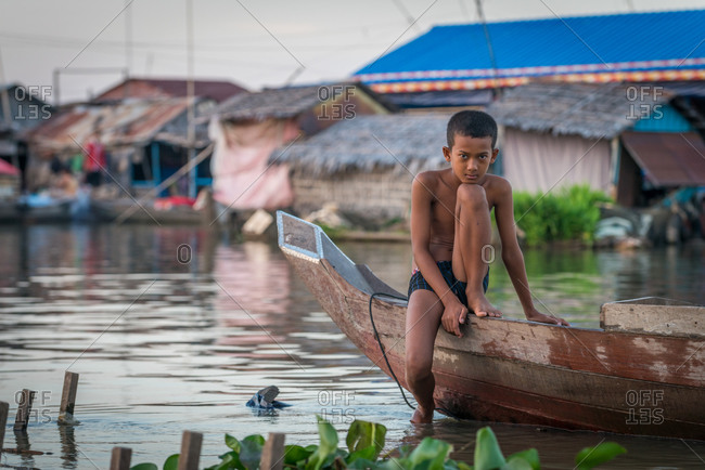 Floating Village, Kompong Chnang, Cambodia - 15 December 2014: Young Boy Sat On Wooden Fishing Boat Amongst Floating Houses.