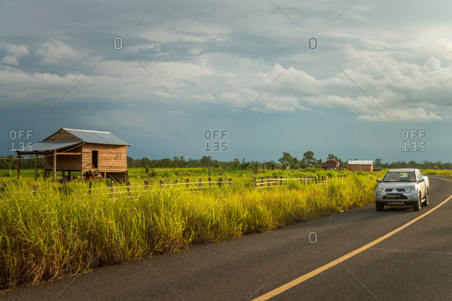 Country Road, Cambodia - 12 August 2013: Modern Car Passes Traditional House On New Road.