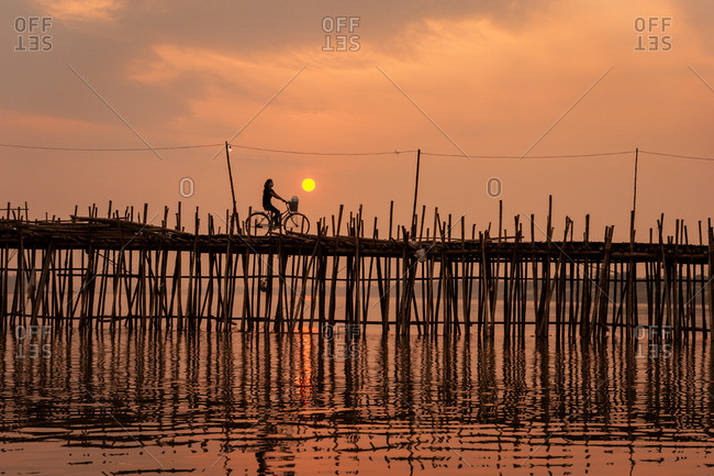 Cambodian Lady On Bike At Sunset, Ko Paen Bamboo Bridge, Kompong Cham, Cambodia. A Temporary Bamboo Bridge Is Reconstructed Every Year To Span A Contributory To The Mekong From Main City To An Island.