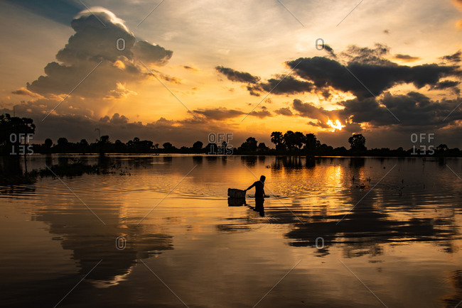 07 Silk Island (Koh Dach), Cambodia - 07 February 2014: Silhouette Of Man Collecting Washing Water From Lake At Sunset.