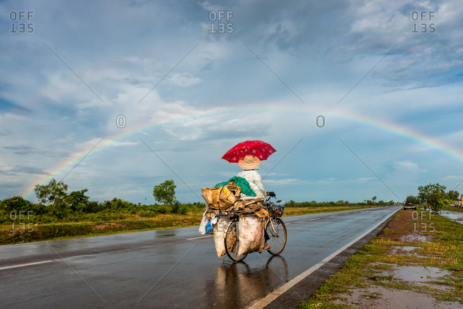Collecting Recyclables, Cambodia - 25 October 2014: Local Cambodian Lady Looks For Trash Under A Rainbow.