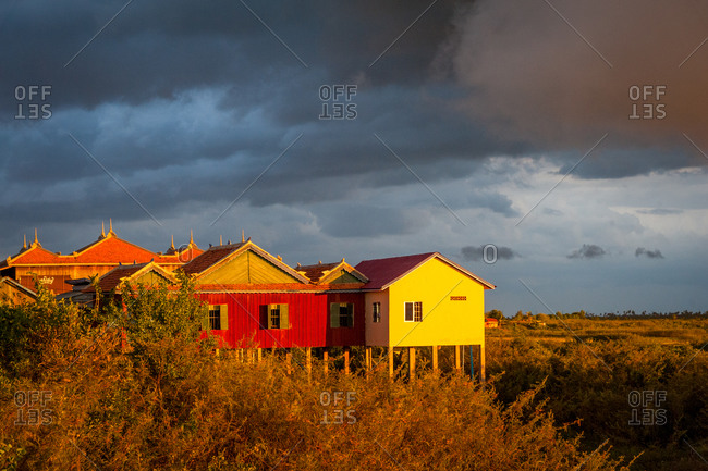 Sunset, Udong, Cambodia - 15 July 2012: Brightly Colored Houses Catch Sun In Dramatic Sunset With Cloudy Sky.