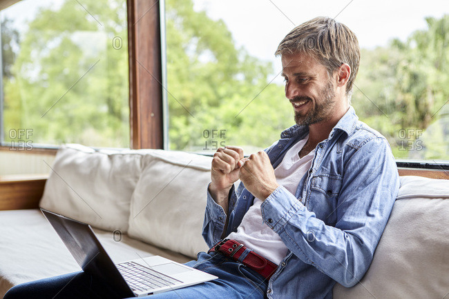 Cheerful mid adult man using laptop