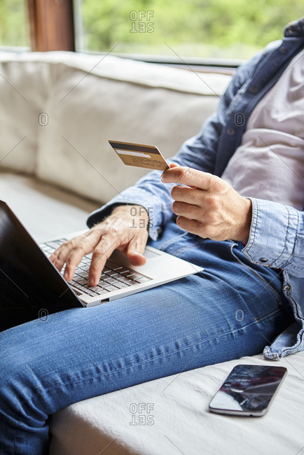 Mid section of mid adult man making online payment