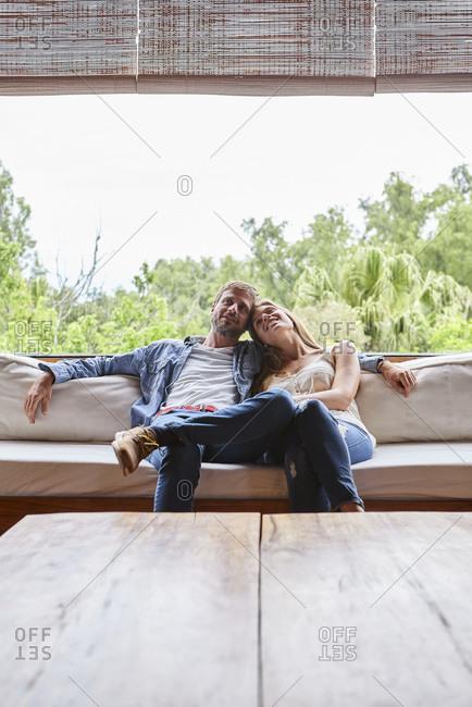 Thoughtful couple sitting on sofa