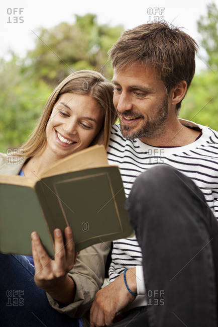 Couple reading book while sitting on bench