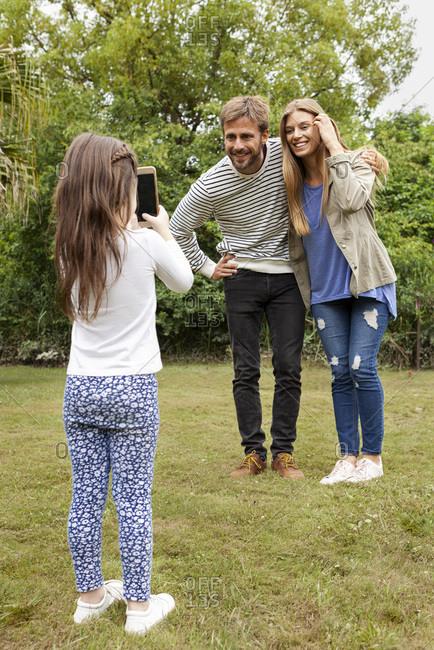 Girl taking photo of her parents in garden