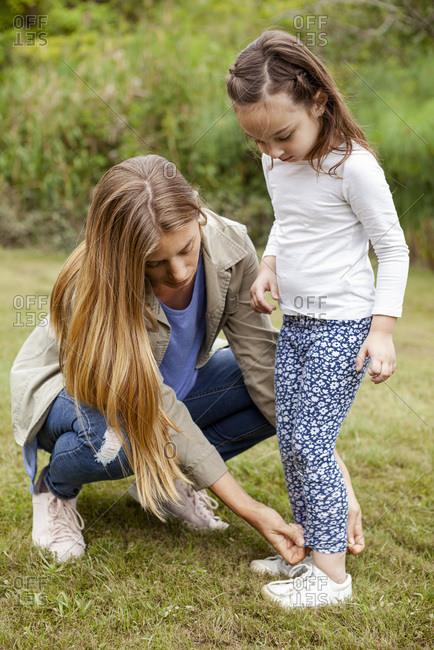 Mother adjusting leggings of her daughter