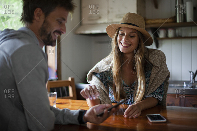 Smiling couple using smartphone at home
