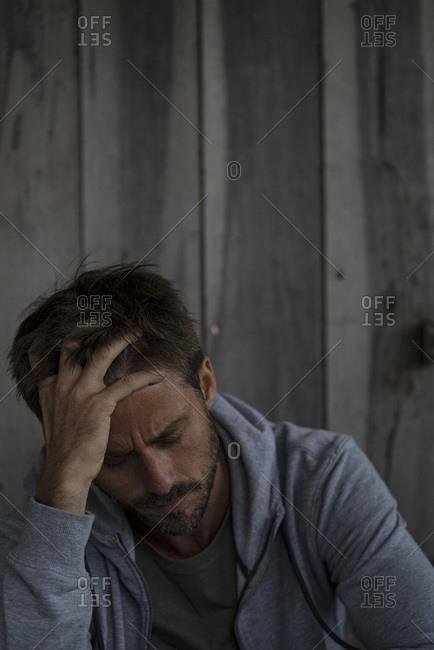 Sad man sitting in stilt hut