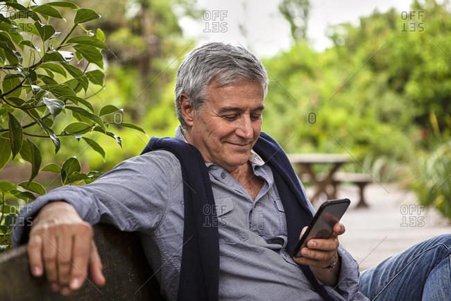 Smiling senior man using phone