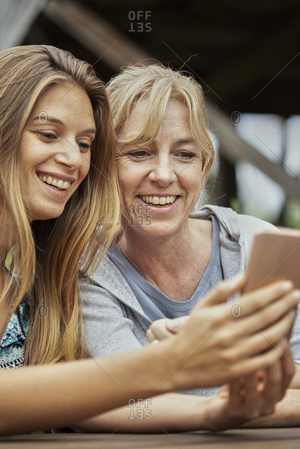 Woman with her mother in law using smartphone