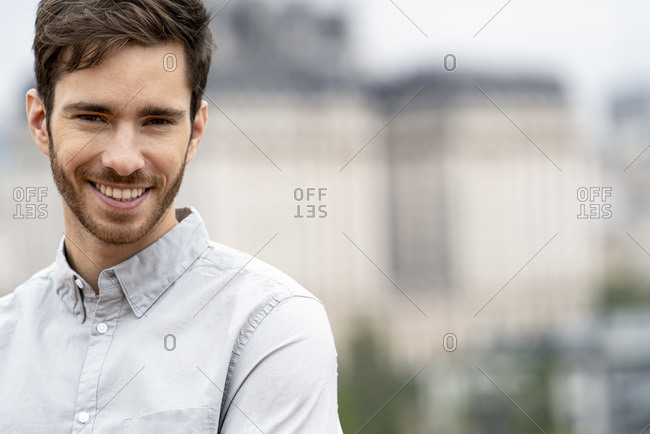 Smiling young man standing alone