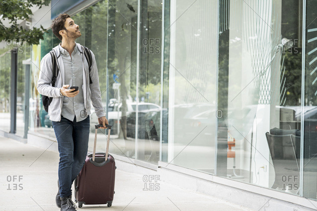 Young man with luggage walking on footpath