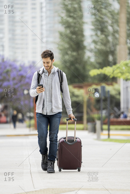 Young man with luggage walking on pavement