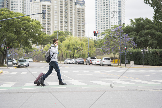 Young man with luggage crossing street
