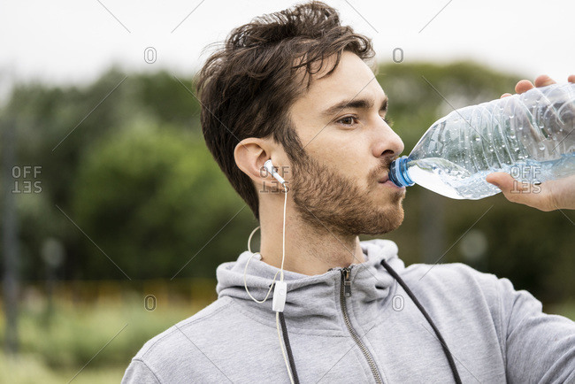 Young man drinking water to quench his thirst
