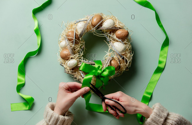 Woman hands wrapping an easter wreath with an eggs