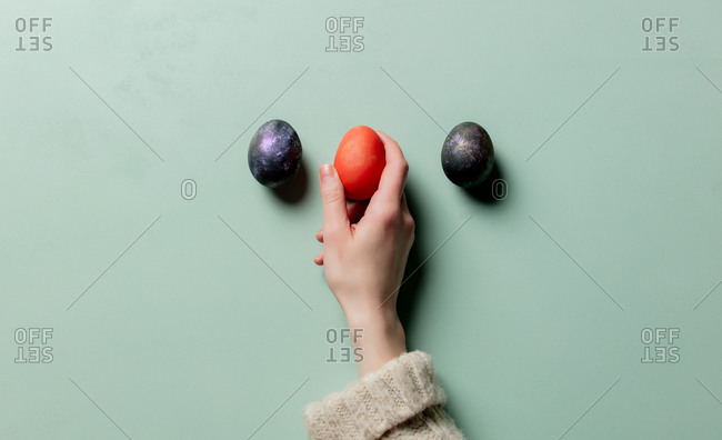 Female hand hold easter eggs on turquoise background