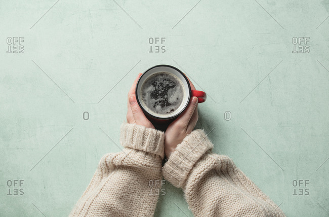 Female hand hold red cup of coffee on turquoise background
