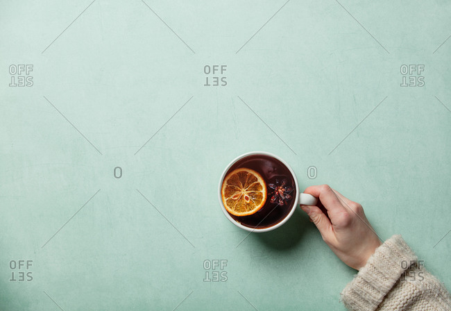 Female hand hold cup of tea on turquoise background
