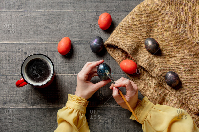 Female brushing an easter eggs and drink a coffee