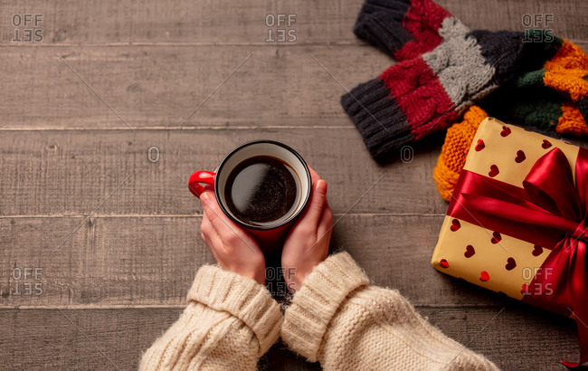 Female hand hold cup of coffee near gift and scarf on wooden table