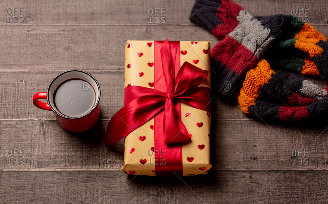 Gift box and cup of coffee next to scarf on wooden table