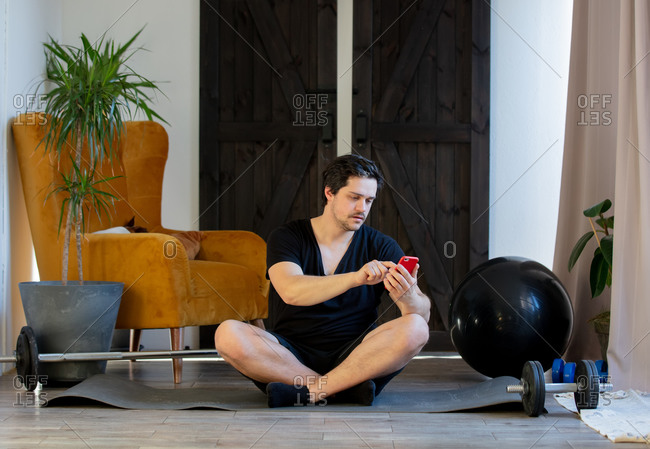 Guy using mobile phone before workout at home