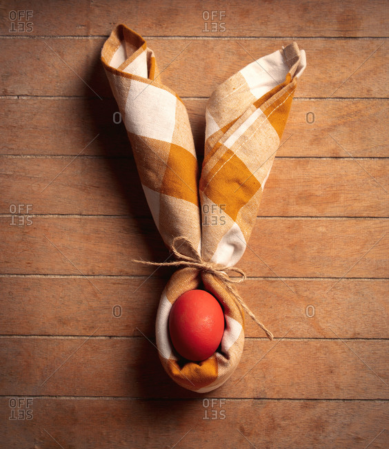 Easter egg and napkin in barrit ears shape on wooden table