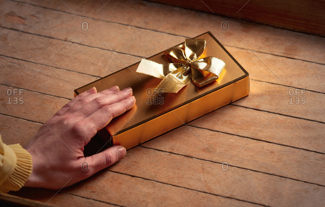 Female hand hold golden gift box on wooden table
