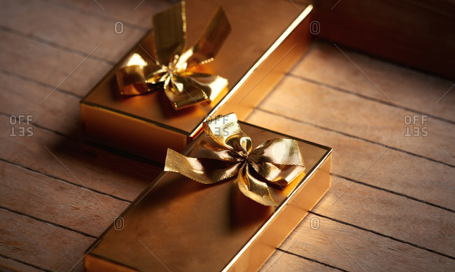 Golden gift boxes on wooden table. side view
