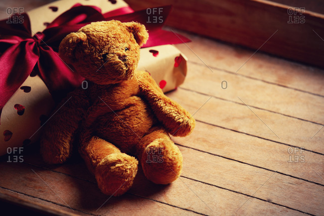 Handmade gift box and teddy bear toy on wooden table