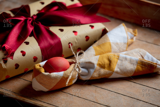 Gift box and easter egg in napkin on wooden table