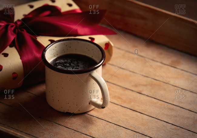 Cup of coffee and gift box on wooden table